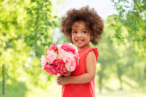 childhood and people concept - happy little african american girl with flowers over green natural background - 258912922