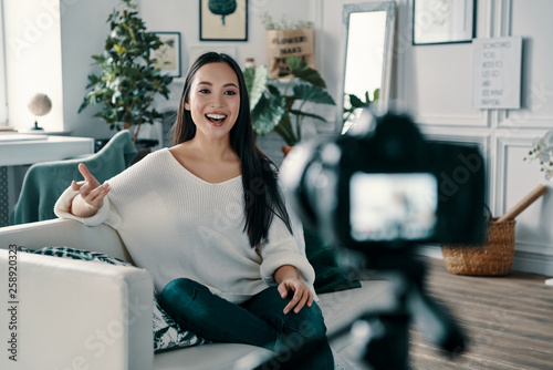 canvas print picture Sharing some fresh ideas. Beautiful young woman gesturing and smiling while making new video for her blog
