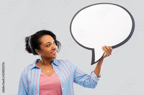 Leinwandbild Motiv people and communication concept - happy african american young woman holding big blank speech bubble over grey background