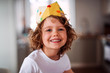 A small girl with a paper crown at home, looking at camera.