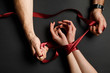 cropped view of man tying red satin ribbon on female hands on black background