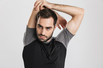Young sports fitness man posing isolate over white wall background make stretching exercises. © Drobot Dean