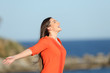 Leinwanddruck Bild - Happy woman in orange breathing fresh air in the coast