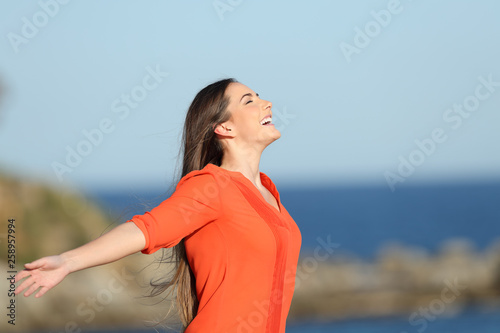 Leinwanddruck Bild Happy woman in orange breathing fresh air in the coast