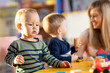 Leinwandbild Motiv Nursery babies playing blocks toy with teacher in kindergarten