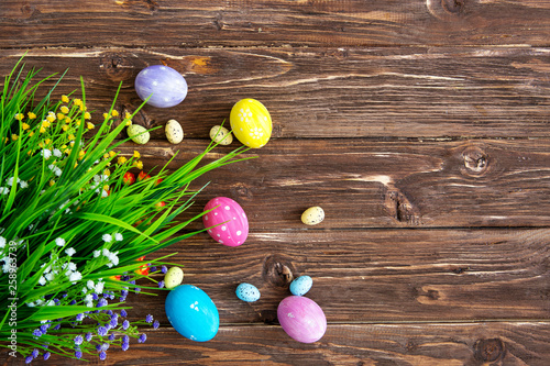 Hand-painted easter eggs with tulips on wooden background - 258963739