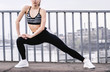 Confident attractive fitness woman in stylish sportswear doing stretching after morning jog on bridge. Beautiful young sports girl warming up before running outdoors. Doing workout, exercising
