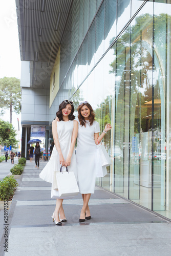 fototapeta na ścianę Friends go shopping. Two young women walk on shopping mall with bags