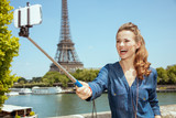 smiling solo tourist woman taking selfie using selfie stick