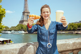 happy young woman showing cup of coffee and croissant