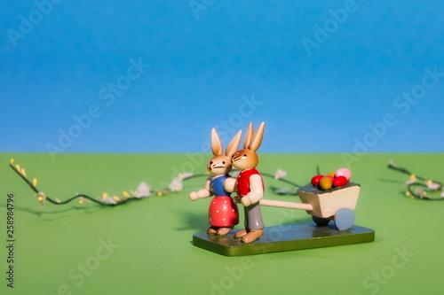 canvas print picture Osterhasenpaar mit einem Wagen voll Ostereier