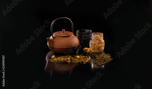 Chinese teapot and tea cups with tea leafs on black background © LotosVideo