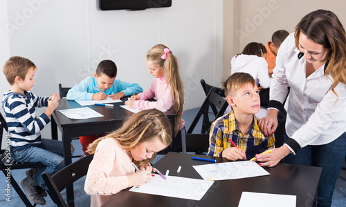 Little children with friendly teacher drawing in classroom - 259005114