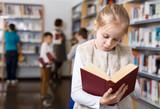 Preteen girl browsing textbook