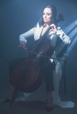 Beautiful woman in a white coat plays the cello
