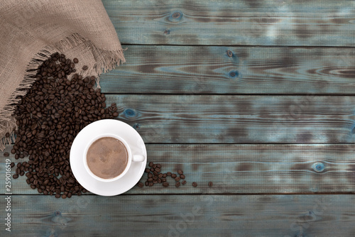 Roasted brown coffee grains and a cup of coffee lie on blue wooden boards. © arthurkochiev