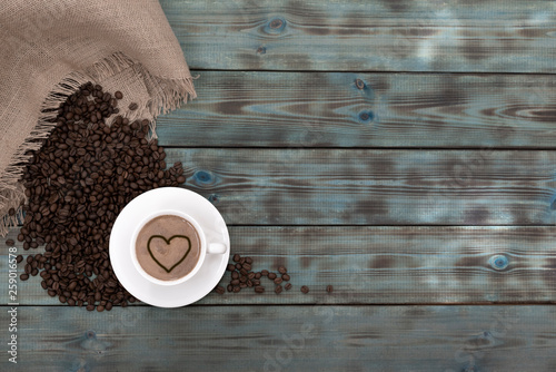 Roasted brown coffee grains and a cup of coffee lie on blue wooden boards.