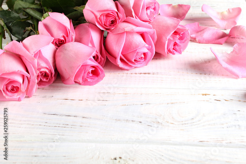Bouquet of roses on a wooden background - 259025793