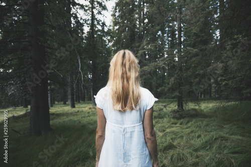White dressed woman, alone in magic forest.