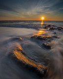 Orange sunrise over the Atlantic as waves wash over rocks on the shore. Photo by: Chuck Beyer