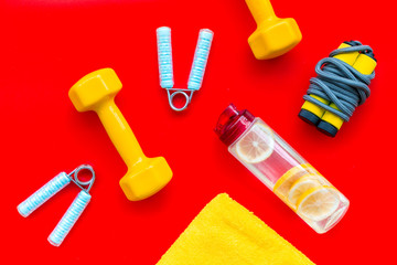 Sport with bars, towel, water and wrist builder red background top view