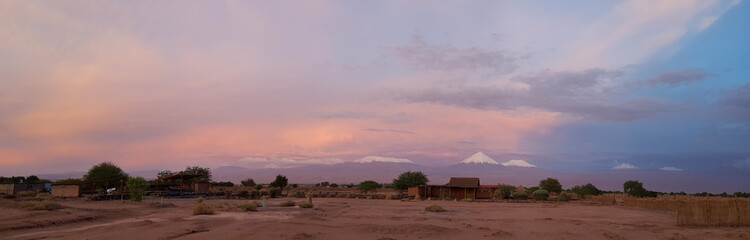 Sunset lights in the arid and desolate landscape of the Atacama Desert and the peaks of the snowy volcanoes of the Andes cordillera in the background