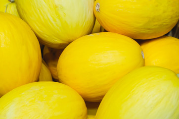 yellow melons stacked for retail sale