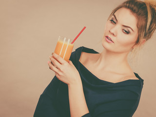 Thinking woman holding fresh orange juice