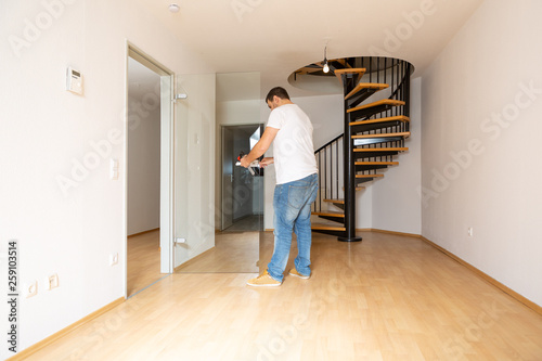 Junger Mann befestigt die Klinke an einer Glastür, im Eingang zu einer Maisonette Wohnung © levelupart