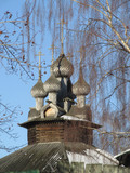 Wooden church in Kostroma, Russia on the spring blue sky background seen through the trees