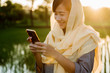 muslim woman with hijab using mobile phone outdoor