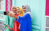 Happy arabian friends using smartphone for making selfie story on social network app - Focus on right girl face