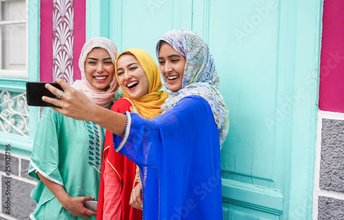 Happy arabian friends using smartphone for making selfie story on social network app - Focus on right girl face © DisobeyArt