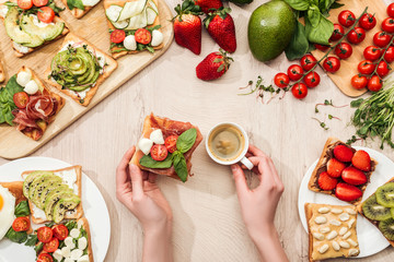 top view of woman holding cup of coffee at table with ingredients, greenery and toasts with vegetables and prosciutto