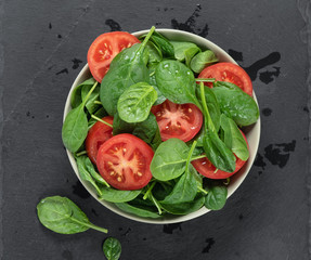 spinach and tomato salad in a bowl on grey stone board. Top view