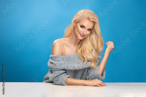 Leinwandbild Motiv Beauty fashion portrait of blonde woman on blue background.