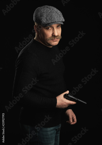 Portrait Of Serious Man With Gun On Black Background.