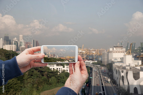 Scenic view of Singapore Hand with a smartphone, on the screen of which the urban landscape