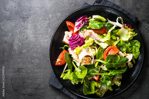 Green salad with chicken and vegetables on black. - 259140516