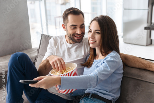 Photo of caucasian couple eating popcorn from bucket while sitting on couch indoor and watching movie