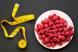 Raw raspberries on plate, measuring tape on black background, top view. Healthy eating and dieting. From above, overhead.