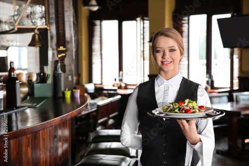 Leinwandbild Motiv Young female waiter with salad in restaurant