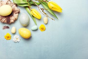 Osternest und Ostereier mit Tulpen auf Hintergrund in blau, Osterkarte
