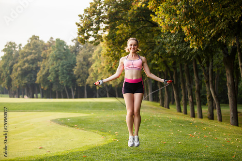 canvas print picture sport girl making exercises outdoors. Young sport woman in a park. Sport and fitness on open air. Exercise lunge leg on the grass and stretching