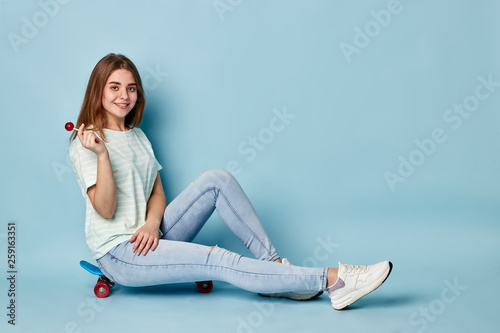 Leinwandbild Motiv blonde girl with chupa chups sitting on a skateboard