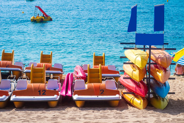 Kayaks and catamarans on the sea in Lloret de mar, Costa Brava, Spain. Leisure rest on sea vacation