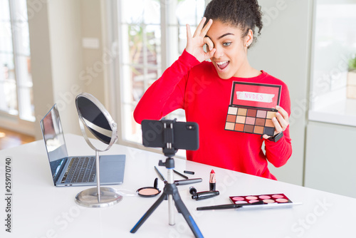 Leinwandbild Motiv Young african american influencer woman recording make up tutorial with happy face smiling doing ok sign with hand on eye looking through fingers