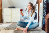 Woman having glass of wine in front of Hi-Fi speakers