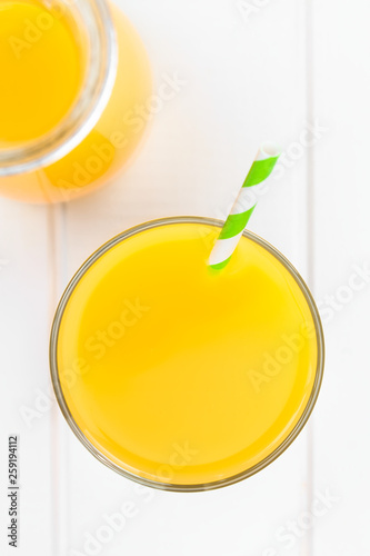 Orange juice in glass with drinking straw, photographed overhead on white wood (Selective Focus, Focus on the glass rim and the top of the juice) © Ildi