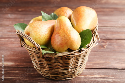 Ripe pears and green leafs in basket on brown wooden table - 259196582